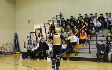 The mascot waving glow sticks in the South Gym.