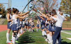 The team creates an arch out of sticks for their seniors.