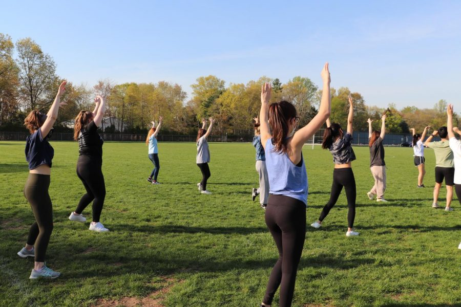 The cast rehearses outside on the soccer field.