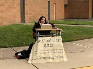 Ava Petrilli, senior class president, selling Gold Cards in front of the school.